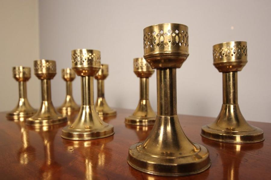A Run of 8 Decorative Brass Candlesticks
